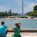 Washington, DC - August 9, 2019: Young adult tourists enjoy the view of the Washington Monument and National Mall from the US Capitol building reflecting pool