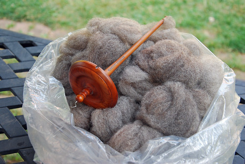 Kundert top-whorl drop spindle and hand-combed grey Romney wool top in plastic bag on a table
