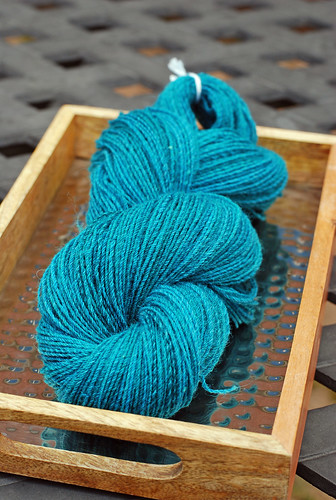 Handspun skein of Southdown blended with Silk yarn in a tray with metal background and wooden frame