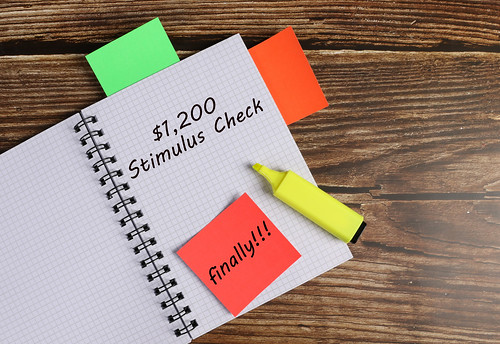 Notebook with $1.200 Stimulus Check text on wooden background