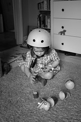 Helmet still on, playing with dolls