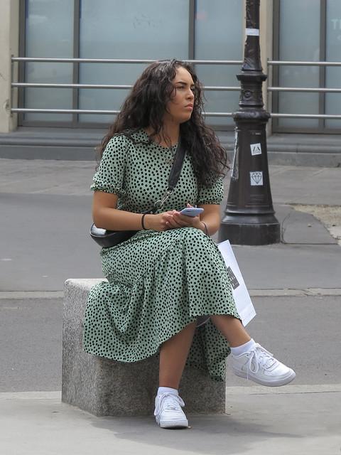 Elegant girl sitting on a curbstone