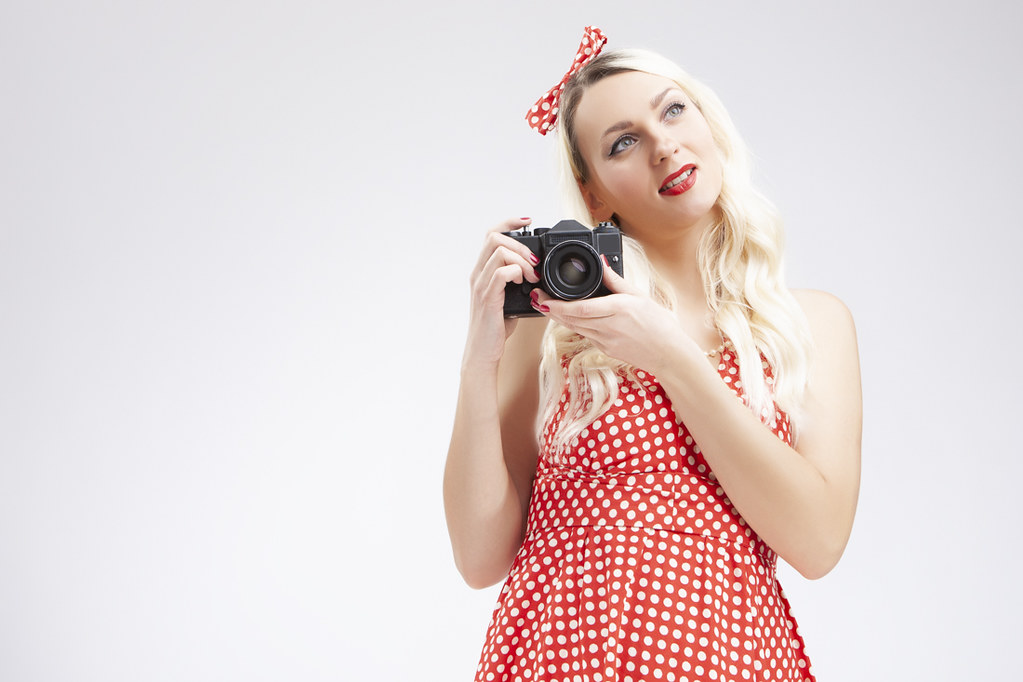 Pin-up Girl Concepts. Caucasian Blond Girl Posing in Pin-up Style and Holding Retro Film Camera in Hands. Against White.