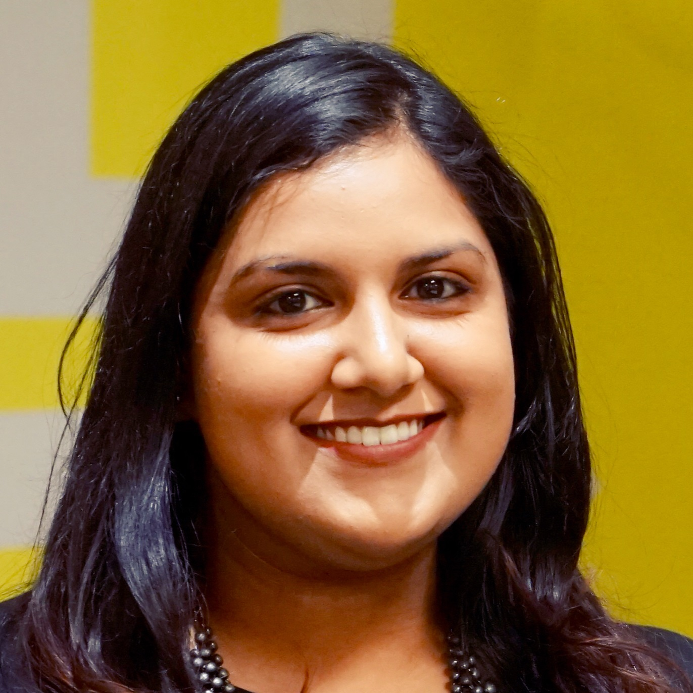 Photograph of Dr Varala Maraj smiling at the camera stood in front of a yellow and white background.
