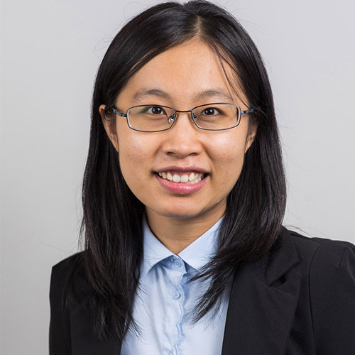 Studio portrait of Dr Meng Meng wearing a black blazer and light blue blouse as she sits in front of a grey background and smiles at the camera.