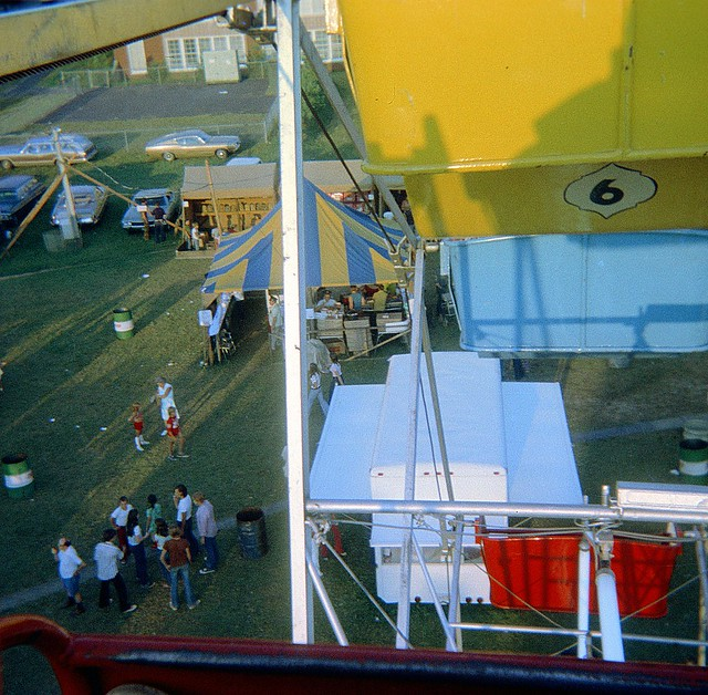 From the top of the Ferris Wheel at a carnival. Can U find a man smoking a pipe, teen smoking a cigarette, two kids dressed identically, two teen girls walking fast, a man frying hamburgers, a 1960s Plymouth Barracuda. North Haven Connecticut. August 1972