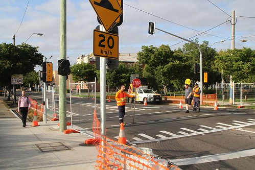Traffic controllers help pedestrians cross at the yet to be commissioned traffic signals on Hampshire Road at the Sun Crescent roundabout