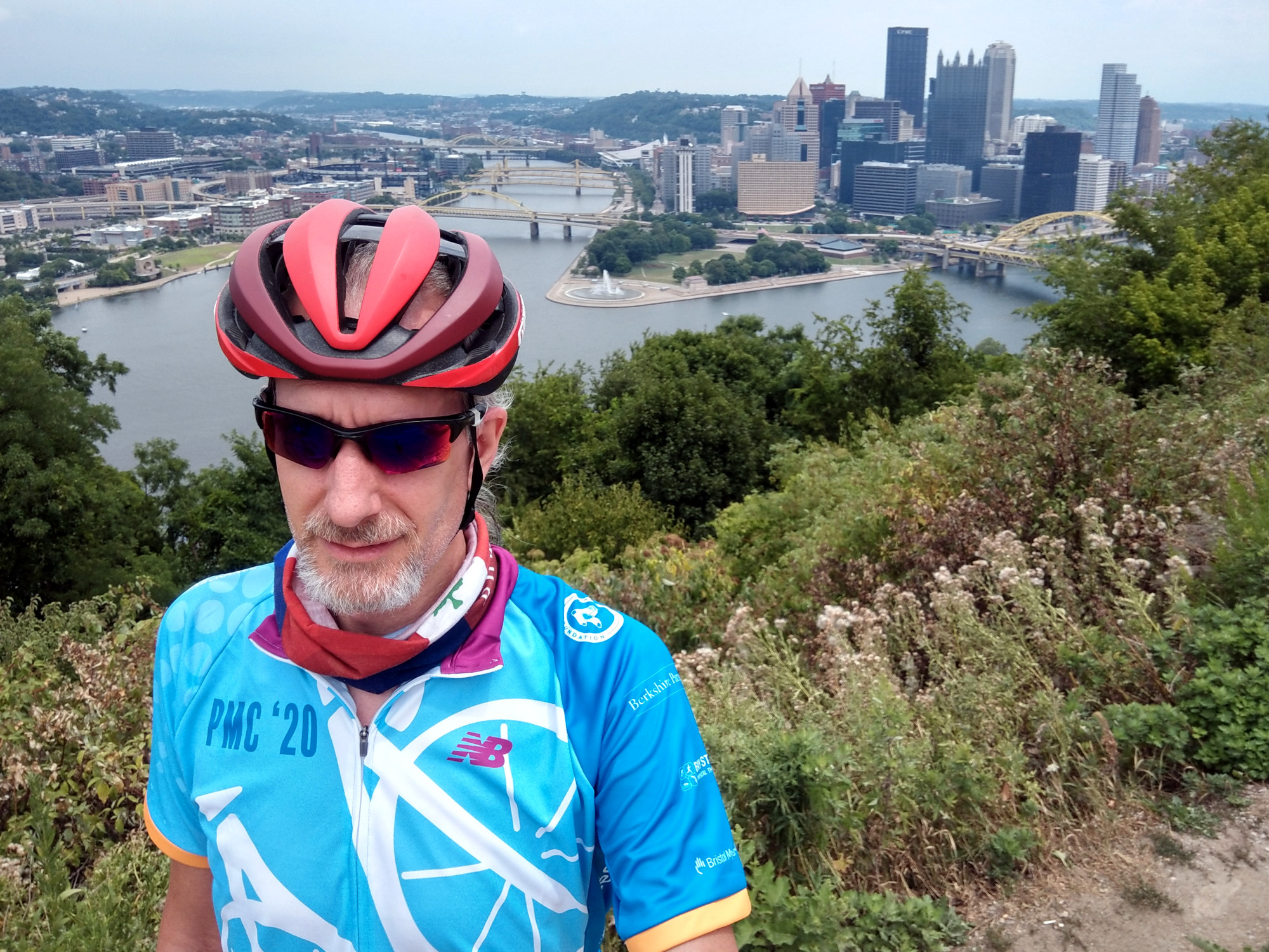 Modeling the 2020 Pan-Mass Challenge jersey on the Grandview Overlook above downtown Pittsburgh