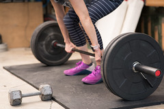 Close up of a woman doing a deadlift.