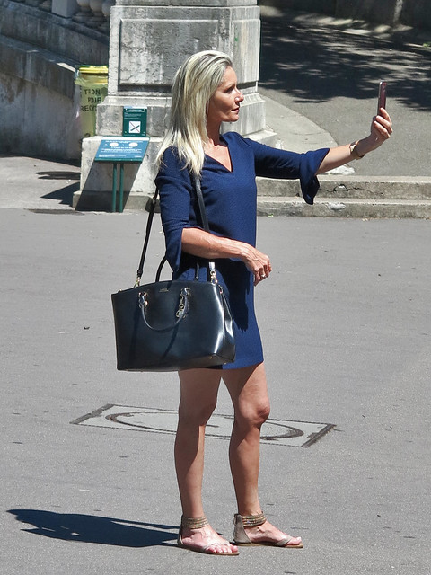 Blonde girl taking a selfie in the square under the Montmartre staircase
