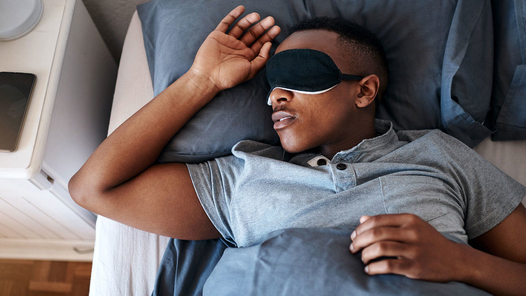 A man asleep in bed wearing an eye mask