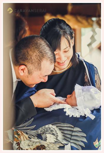 お宮参り 赤ちゃんの顔を覗き込むパパとママ