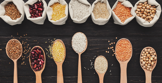Assorted gluten free grains in cloth bags and spoons on rustic wooden background, top view