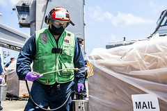 Hospital Corpsman 2nd Class Clint Woods sprays disinfectant on a pallet delivered to USS Germantown (LSD 42) during a replenishment-at-sea. (U.S. Navy/MC2 Taylor DiMartino)