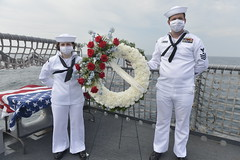 Electrician's Mate 2nd Class Ashley Newman and Mineman 1st Class (SW) Justin Crabtree stand at the ready to ceremoniously set a wreath out to sea aboard USS Indianapolis (LCS 17). (U.S. Navy/PO3 Bea Vang)