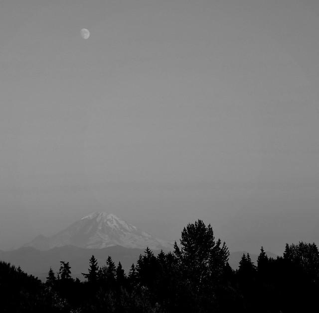 The moon in transit over Mt. Rainier