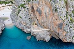 Drone photo: path crossing the steep rock face at the entrance of the canyon. Cala de Sa Calobra, Majorca