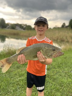 Photo of Boy holdling a largemouth bass