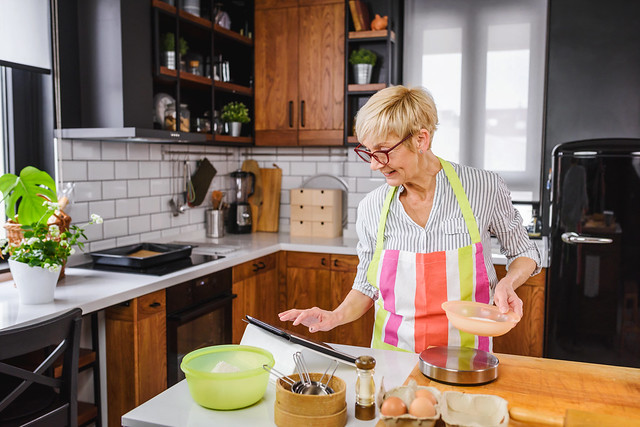 A middle-aged woman cooking in the kitchen using a recipe from her tablet