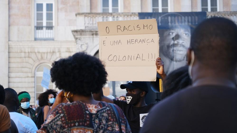 葡萄牙示威者高舉「種族歧視是殖民遺緒」標語。(圖片來源:Ana Mendes/Al Jazeera)