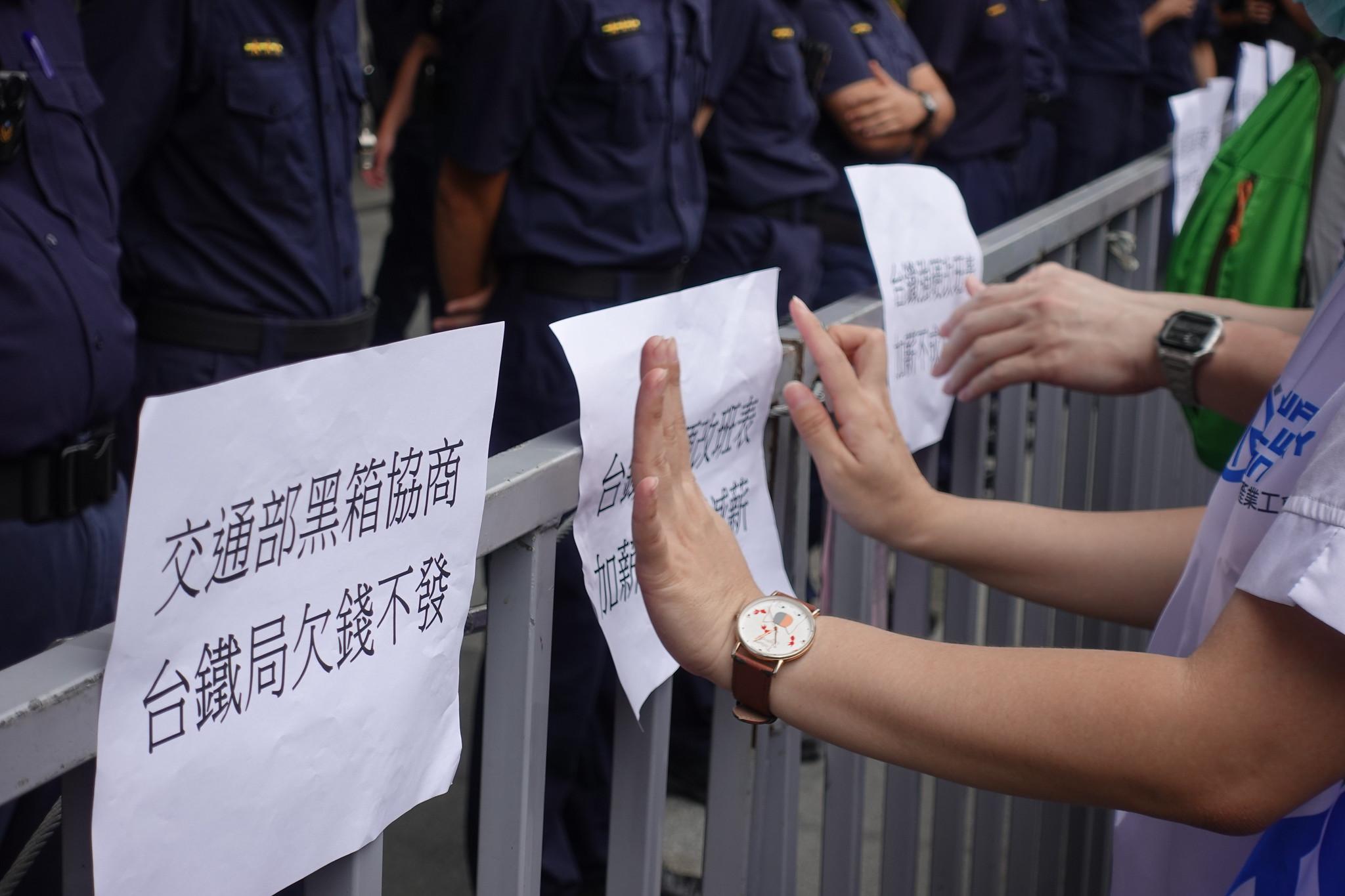 台鐵員工把標語訴求貼在交通部前的柵欄上。(攝影:張智琦)