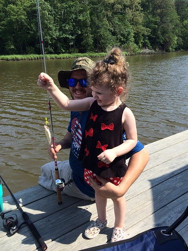 Photo of young girl next to her father and holding a fishing rod with a white perch