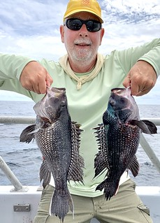 Photo of Man holding two nice black seabass