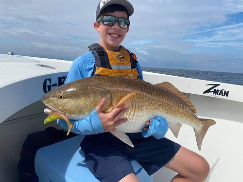 Photo of Boy holding a large red drum on a boat