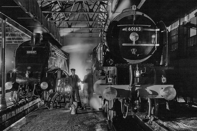 Railway workers stopf for a chat whilst attending to majestic steam locomotives