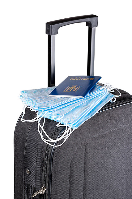 Black suitcase with a stack of medical masks and a passport