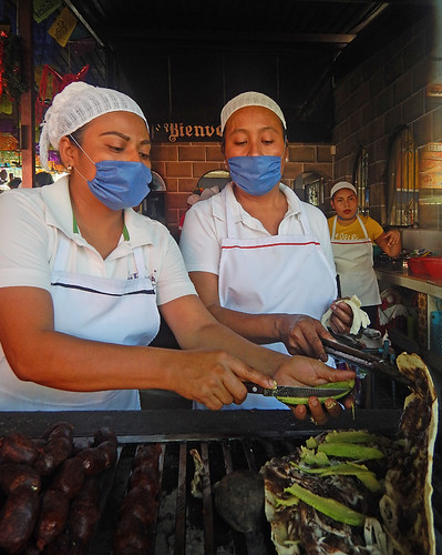 Preparing food while wearing masks at a stall in the Puerto Escondido Market, Mexico