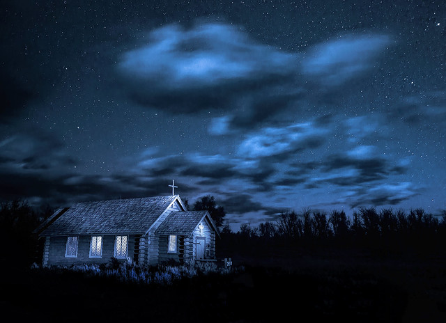 The Chapel of the Transfiguration, a small log chapel in Grand Teton National Park near Jackson, Wyoming at night