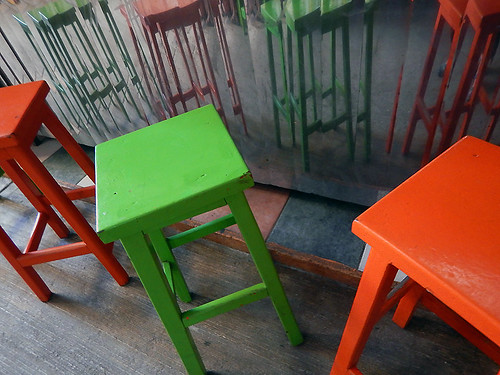 Bright orange and green stools at a freshly-squeezed orange juice stall in the Puerto Escondido Market, Mexico