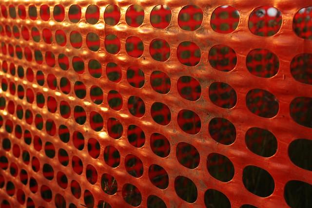 Orange plastic fence: light, shadow, and pattern