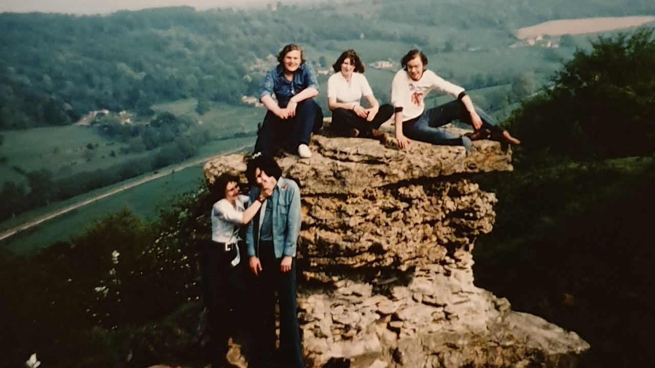 Group of students in front of a rock