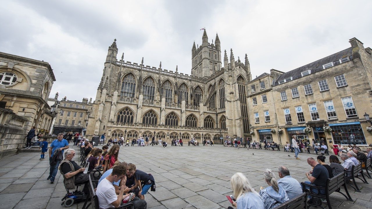 People sat on benches around Bath Abbey