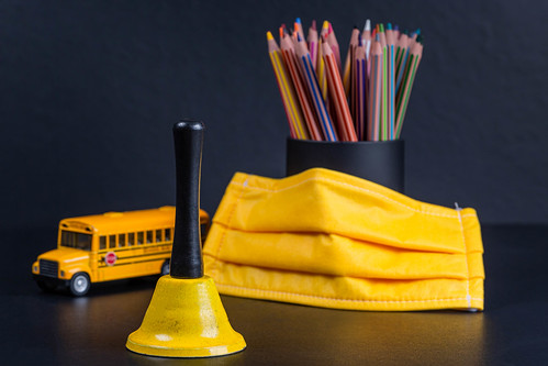Yellow bell, mask, school bus and pencils as a symbol of the beginning of the new school year | by wuestenigel