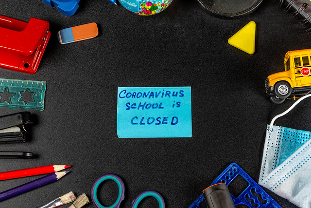 Frame of school supplies on a black background with the inscription-coronavirus school closed