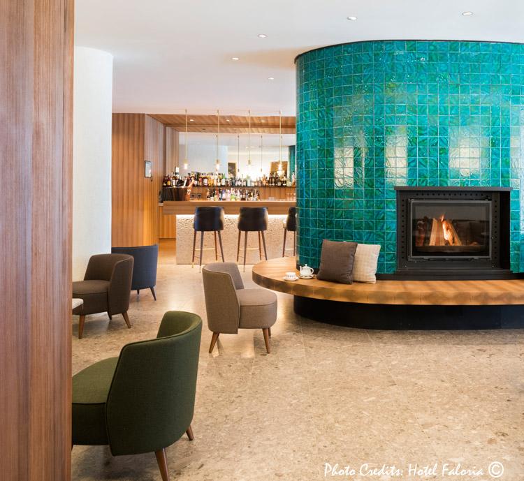 O hall de entrada do Hotel Faloria com o Louge bar onde podemos degustar excelentes drinks. A decor utiliza materias primas locais e a cor verda da lareira lembra o verde da natureza ao redor do hotel.