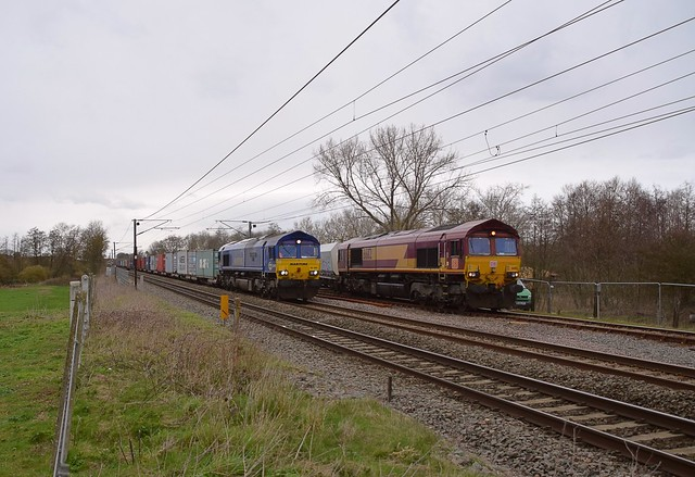 66005 'Intermodal One' heads the Wakefield Europort - Felixstowe South Intermodal past Barham, where 66112 is unloading the Mountsorrel Stone. 04 03 2020