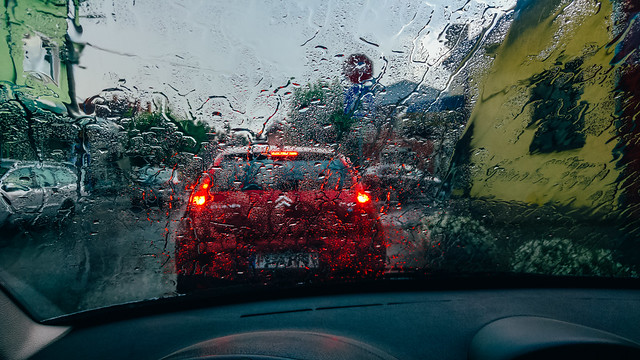 Poor visibility due to water flowing down the car's windshield. Driving in heavy rain