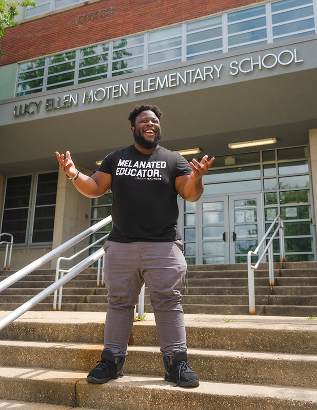 "Photo showing a man standing on steps in front of a school building, wearing a shirt that says ""Melanated Educator,"" and gesturing while laughing."