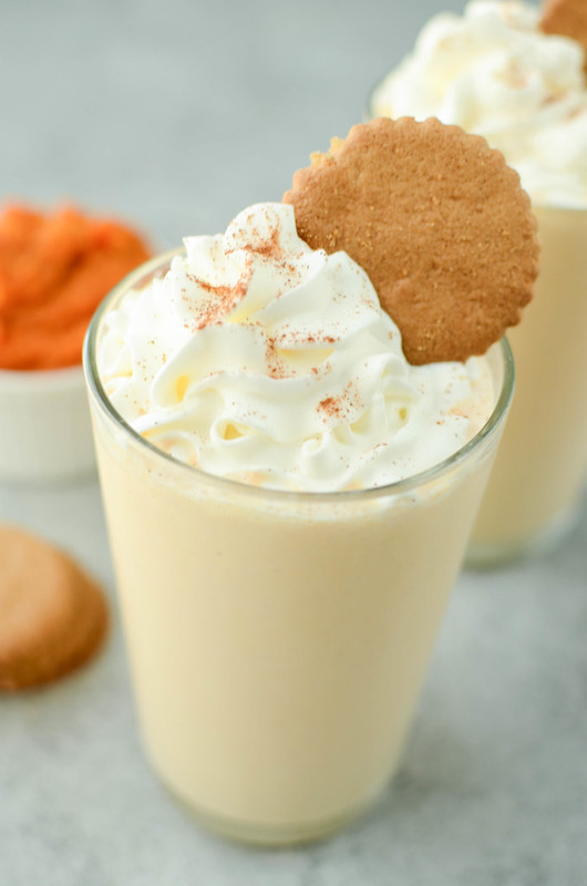 Pumpkin pie milkshake in a clear glass topped with whipped cream, pumpkin pie spice, and a gingersnap cookie