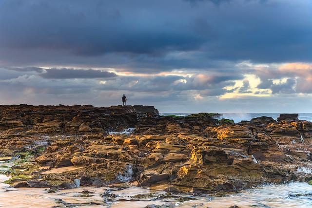 Rain Clouds, Surfer o the Rocks and a Sunrise Seascape