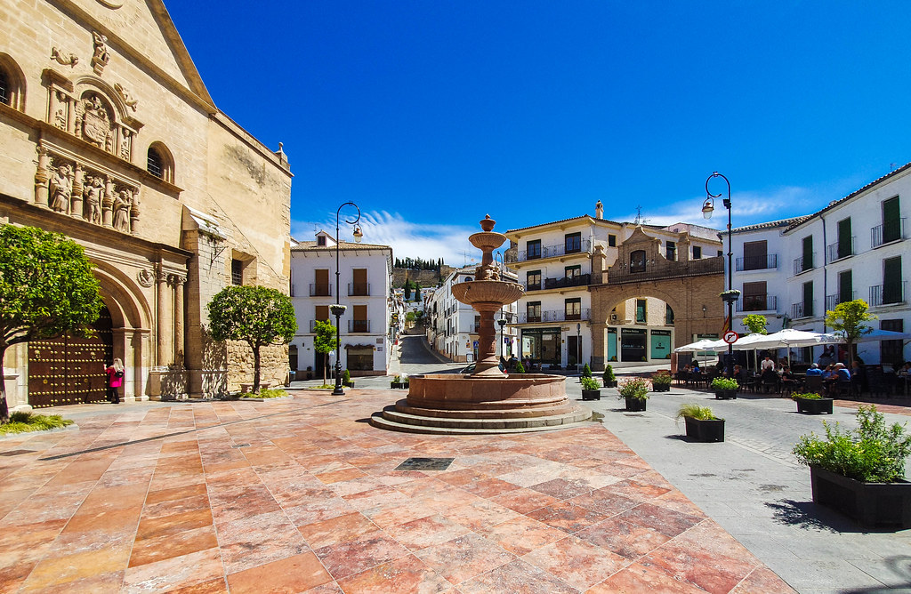 one of the squares in Antequera, with a fountain with two tiers in the middle  and a church on the left hand side of the screen. The square is surrounded by white buildings, broken by streets going uphill. One of the streets has an arch with what resembles a bell and two towers at the entrance.