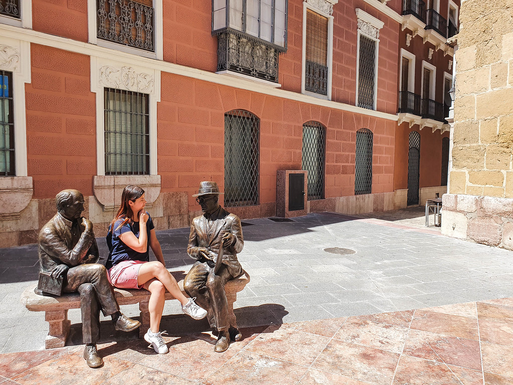 A photo of a bench on which sits a statue of two men: one is holding a book in his right hand whilst keeping the left hand under his chin, thinking; the one one of a man who is wearing glasses and hat, and who is pointing at a book. I am sitting between them, imitating the first man. I am wearing a black tshirt and red shorts. The building behind the statue has very large windows and its walls are terracotta colored.