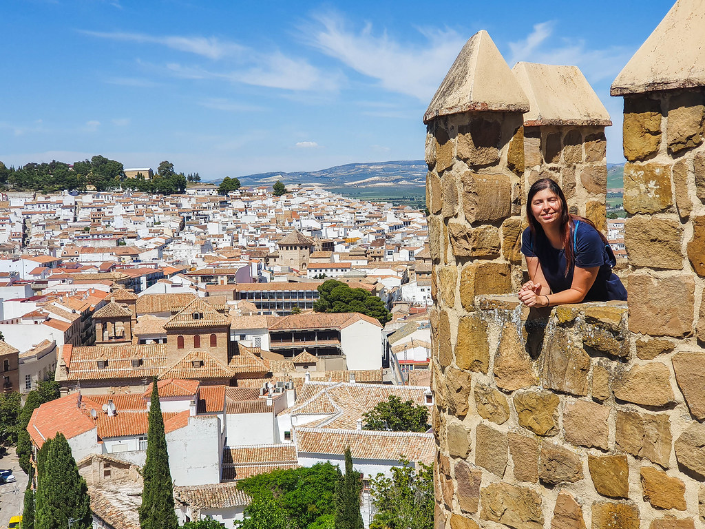 On the right hand side of the picture you can see one of the towers of the Alcazaba and myself looking towards the camera from it. On the left hand side of the photo there is a panorama of the white houses below, which all have terracotta colored rooftops covered with shingles.