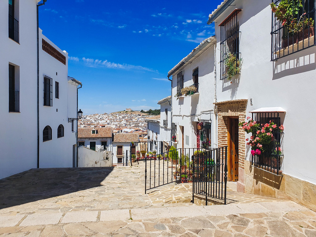 A view of one of the pedestrian streets in Antequera. There is cobbled stone on the ground, white houses on each side, which are decorated with pots of pink flowers.