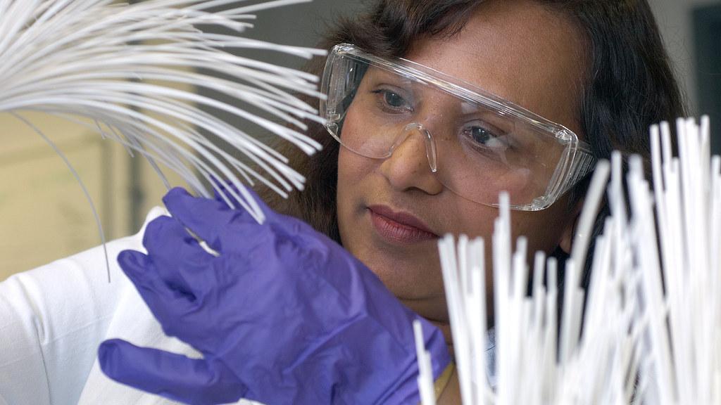A professor examines fibre tubes.