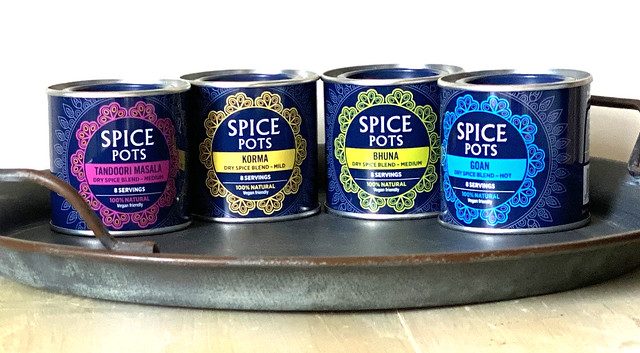A tray holding Spice Pots spice blends in gorgeous decorative tins